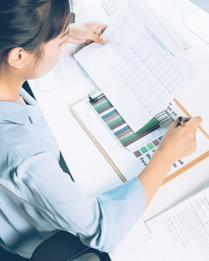 businesswoman analyzing document with pen in office